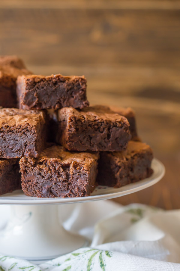 Extra Thick Fudgy Homemade Brownies cut in squares and stacked on cake stand.