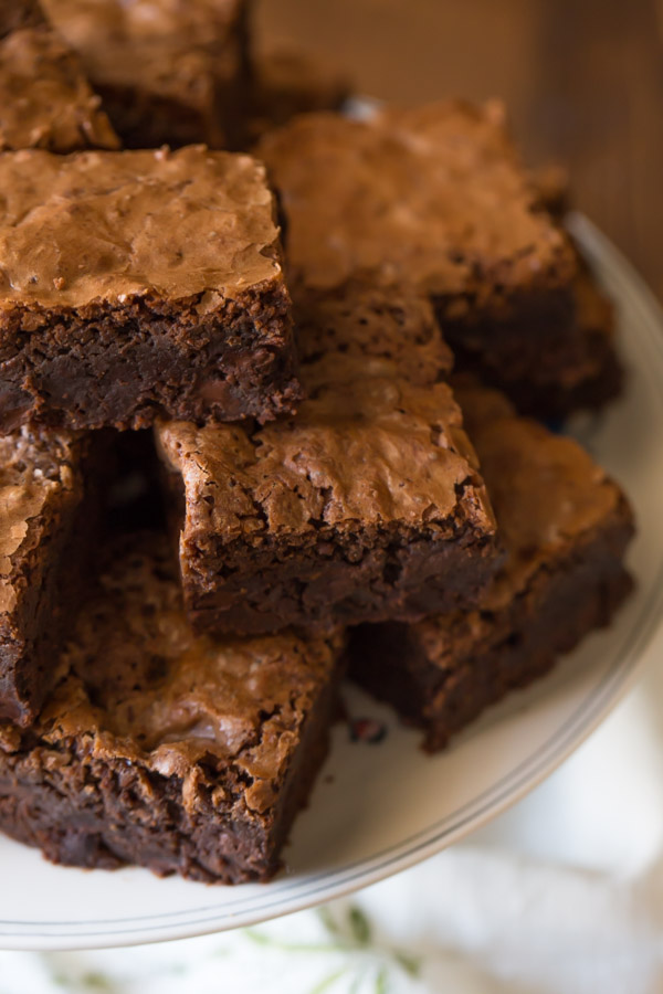 Extra Thick Fudgy Homemade Brownies cut in squares and stacked on a cake stand.