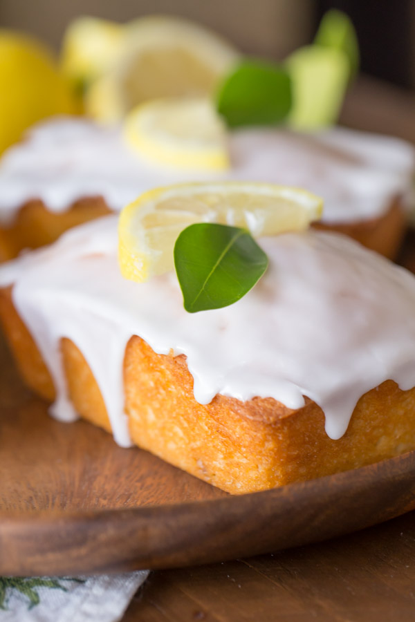 Mini Iced Lemon Pound Cake Loaves garnished with a lemon wedge and green leaf on a wood serving tray.