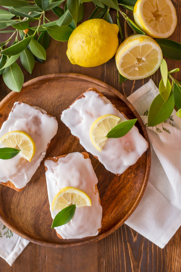 Mini Iced Lemon Pound Cake Loaves garnished with a lemon wedge and green leaf on a wood serving tray, next to some lemons and lemon tree leaves.
