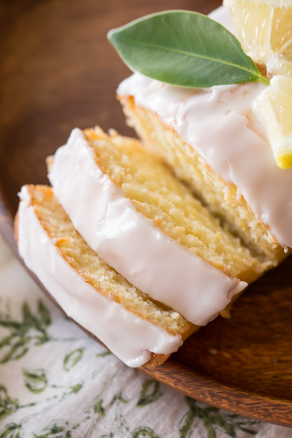 Mini Iced Lemon Pound Cake Loaf garnished with a lemon wedge and green leaf, that has two slices ready for serving.