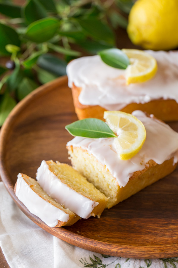 Mini Iced Lemon Pound Cake Loaf garnished with a lemon wedge and green leaf, that has two slices ready for serving, with another whole loaf sitting next to it on the same wood plate.