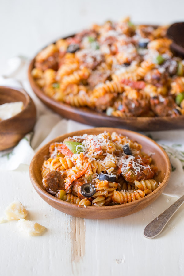 Supreme Pizza Pasta in a wood bowl topped with parmesan cheese, with the serving dish of pasta in the background.