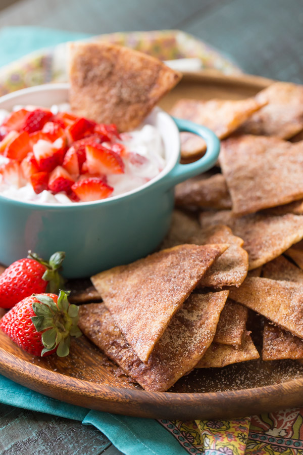 Baked Cinnamon Crisps on a wood plate with a bowl of Creamy Strawberry Dip and a few whole strawberries.