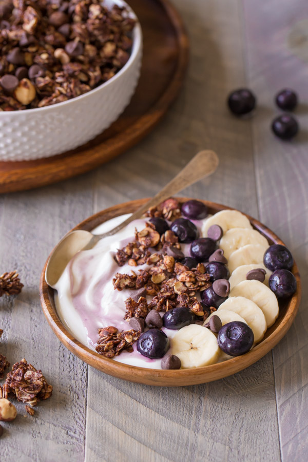 Chocolate Hazelnut Granola Yogurt Bowl with a spoon in it, with a bowl of granola in the background.