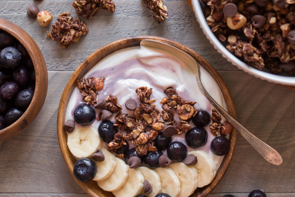 Chocolate Hazelnut Granola Yogurt Bowl with a spoon in it, and a bowl of blueberries and a bowl of granola next to the yogurt bowl.