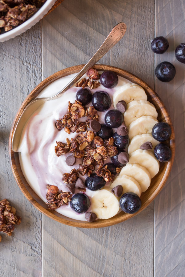 Chocolate Hazelnut Granola Yogurt Bowl with a spoon in it, and some granola and blueberries around the bowl.