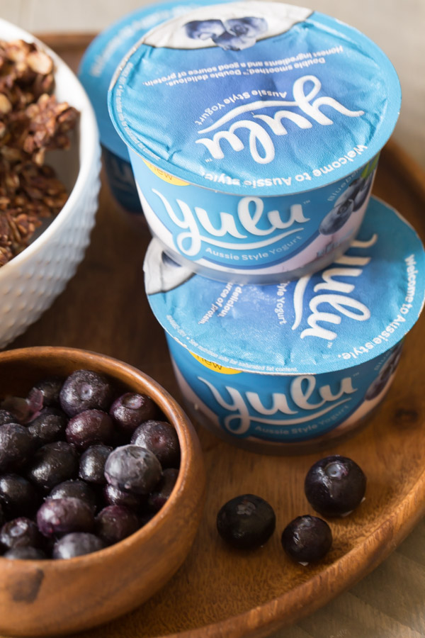 Little containers of Yulu yogurt stacked on a wood tray, along with a bowl of blueberries and and bowl of Chocolate Hazelnut Granola.