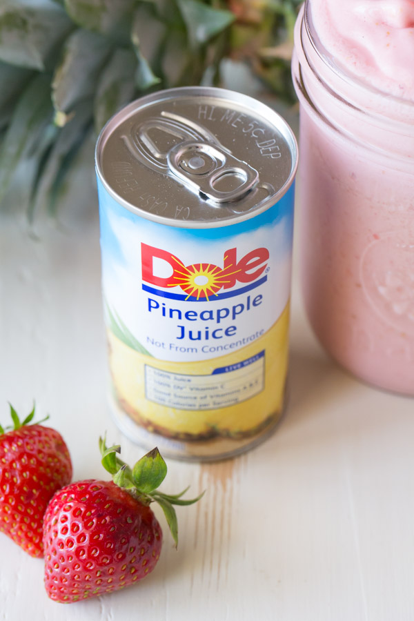 A can of Dole Pineapple Juice, next to a glass jar of Dole Pineapple Strawberry Cream Slush and some whole strawberries.