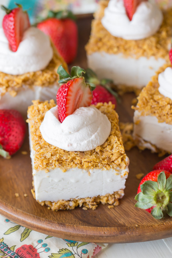 Fried Ice Cream Bars topped with whipped cream and a sliced strawberry, arranged on a wood plate with whole strawberries.