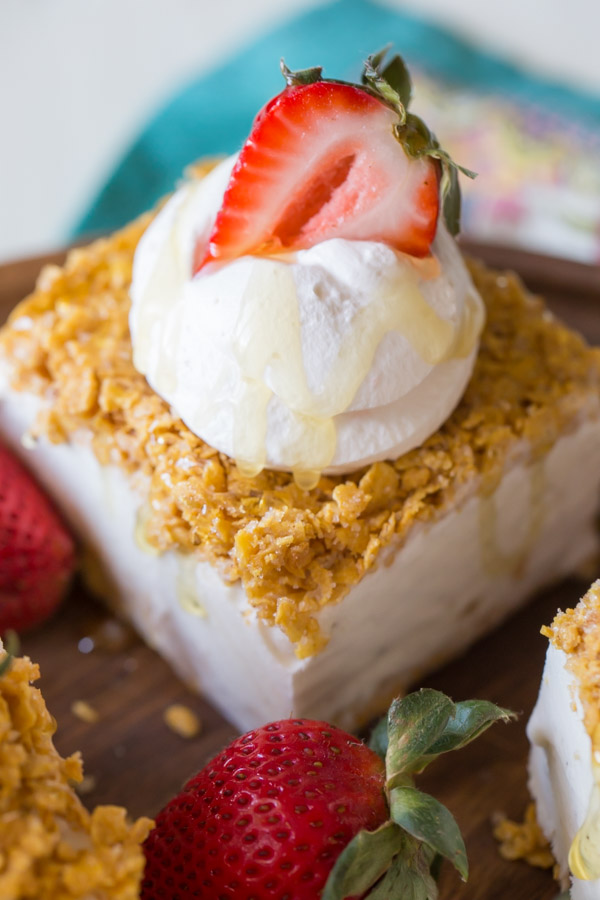 Fried Ice Cream Bar topped with whipped cream, a sliced strawberry and some honey.