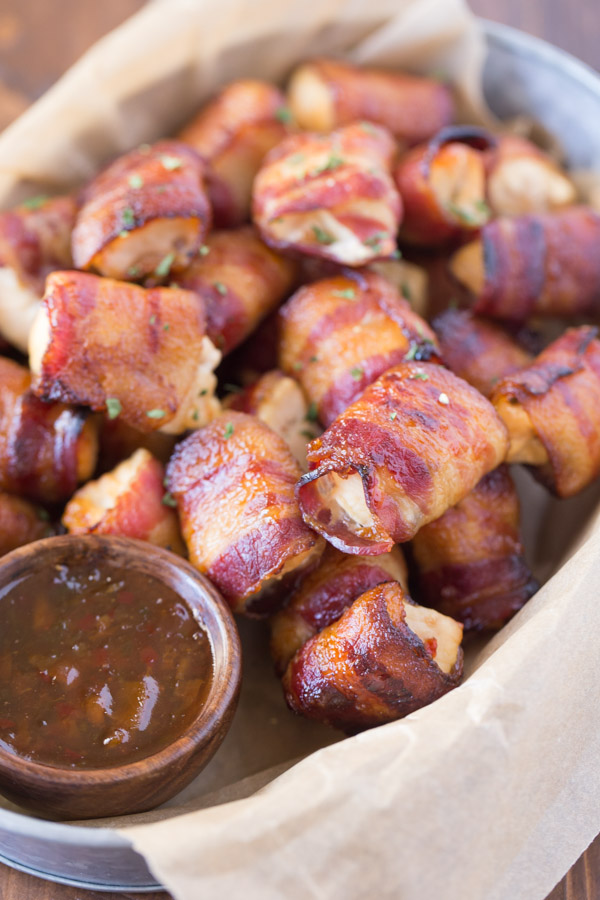 Bacon Wrapped Chicken Bites in a galvanized serving bucket with a little cup of Apricot Pepper Dipping Sauce.