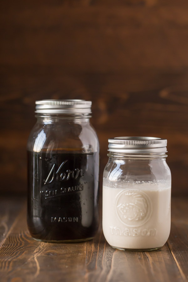 Cold Brew Iced Coffee and Homemade Vanilla Creamer both in mason jars sitting next to each other.