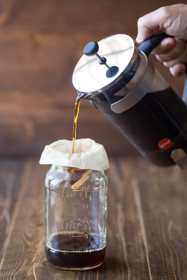 Coffee from a French press being poured through a coffee filter and into a jar.