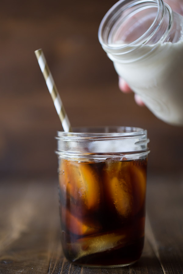 Cold Brew Iced Coffee in a glass jar with a straw, with a jar of Homemade Vanilla Creamer held over the iced coffee about to be poured in.