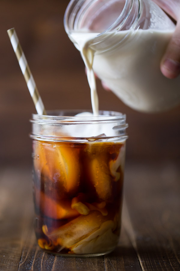Cold Brew Iced Coffee in a glass jar with a straw, and Homemade Vanilla Creamer in a glass jar being poured into the iced coffee.