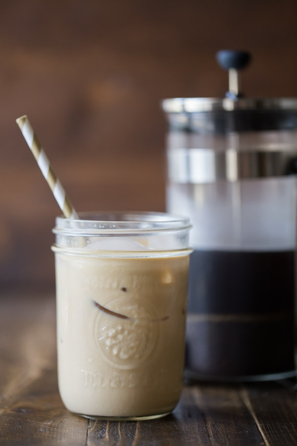 Cold Brew Iced Coffee mixed with some Homemade Vanilla Creamer in a glass jar with a straw, and a French press in the background.