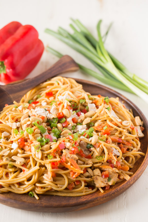 Easy Spicy Peanut Noodles With Chicken on a wood serving plate with a wood serving spoon, and a whole red pepper and a bundle of green onions in the background.