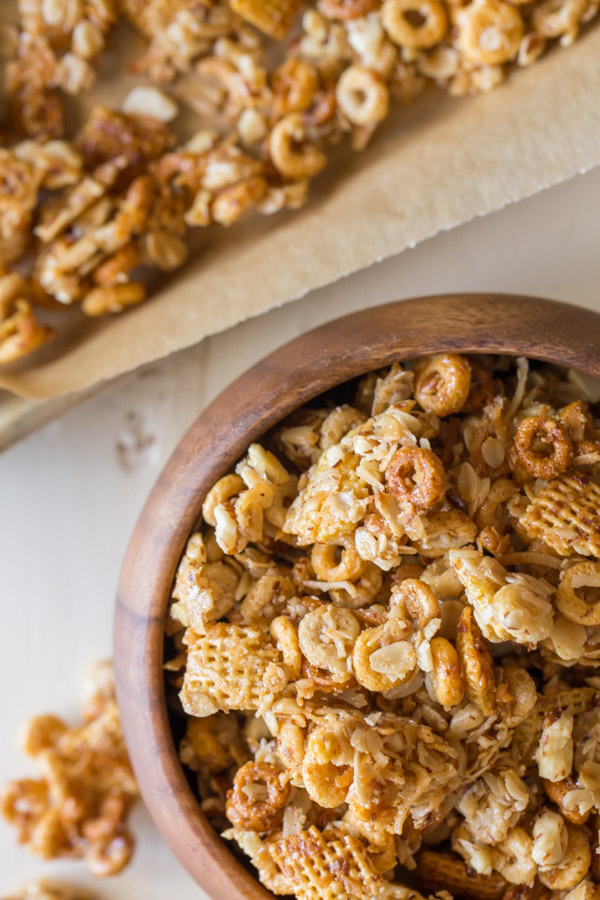 Healthier Coconut Almond Chex Mix in a wood bowl with more Chex mix on a parchment paper lined baking sheet next to the bowl.