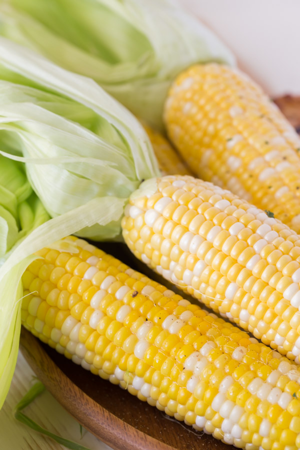 Corn on the Cob that has been cooked in the microwave, with the husks pulled back but still on the ends.