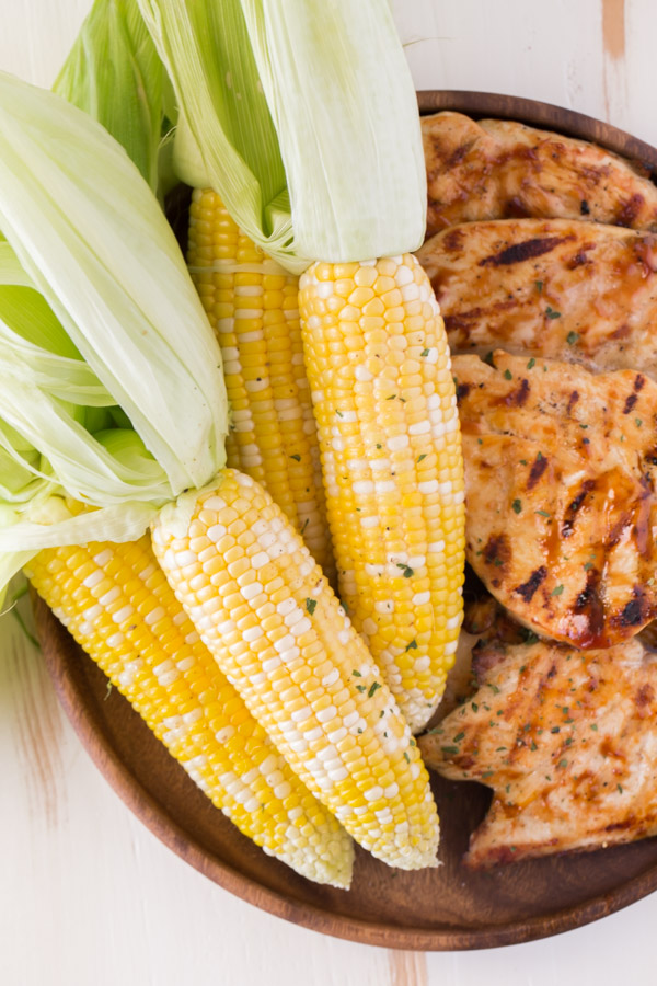 Corn on the Cob that has been cooked in the microwave, with the husks pulled back but still on the ends, sitting on a wood platter with some grilled chicken.