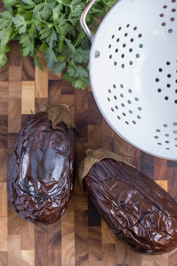 Two whole eggplants that have been broiled, sitting on a cutting board with a colander and some fresh parsley.