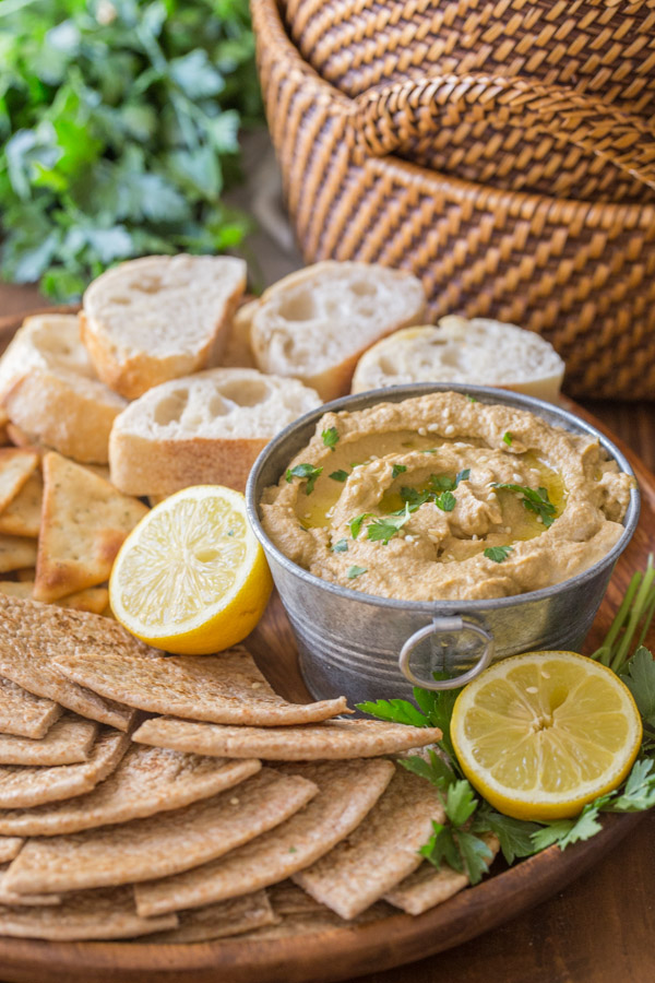 Roasted Eggplant Dip in a galvanized mini bucket for serving, on a wood tray with pita wedges, French bread slices, crackers and a lemon sliced in half.