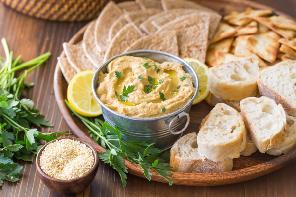 Roasted Eggplant Dip in a galvanized mini bucket for serving, on a wood tray with pita wedges, French bread slices, crackers and a lemon sliced in half, with some toasted sesame seeds and fresh parsley next to the tray.