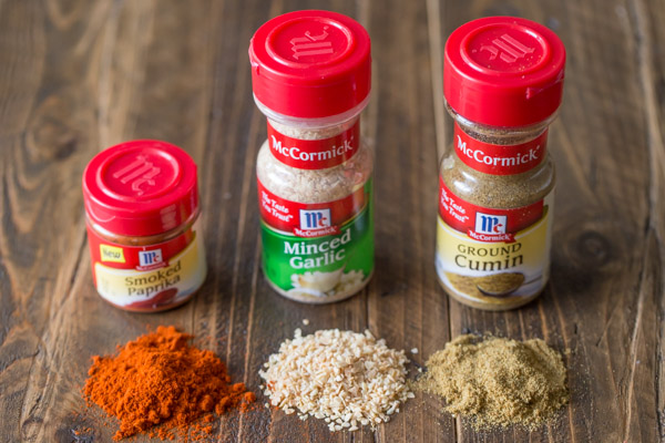 A McCormick Smoked Paprika container, a McCormick Minced Garlic container and a McCormick Ground Cumin container lined up with a pile of the spice in front of each container.