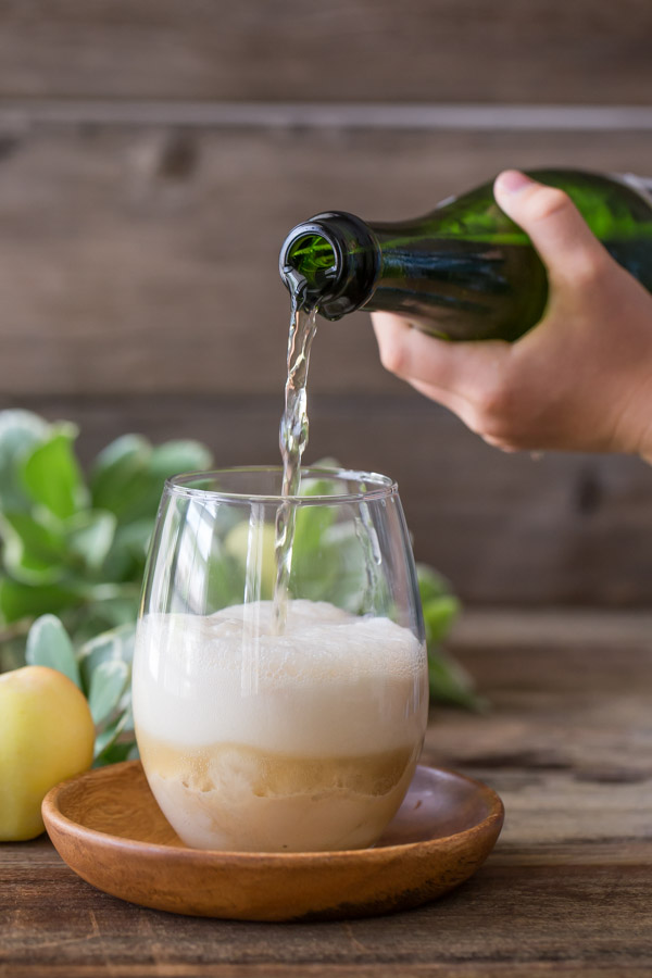 A glass with Salted Caramel Ice Cream in it, and some Sparkling Apple Cider being poured on top.