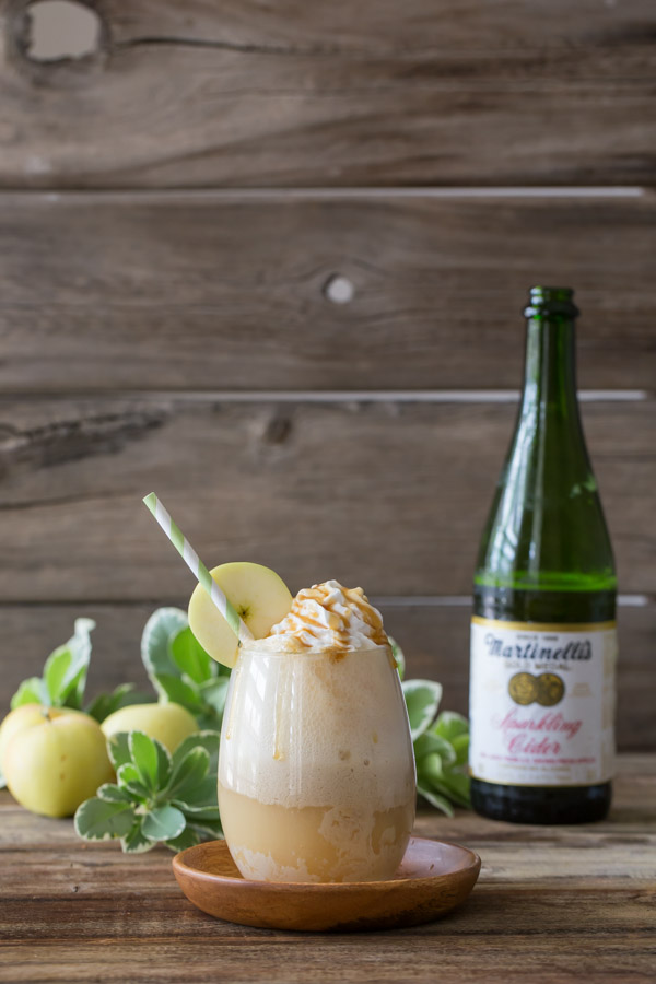 Caramel Apple Float topped with whipped cream and caramel, with a straw and an apple slice on the rim of the glass, and a bottle of Sparkling Cider and whole apples in the background.