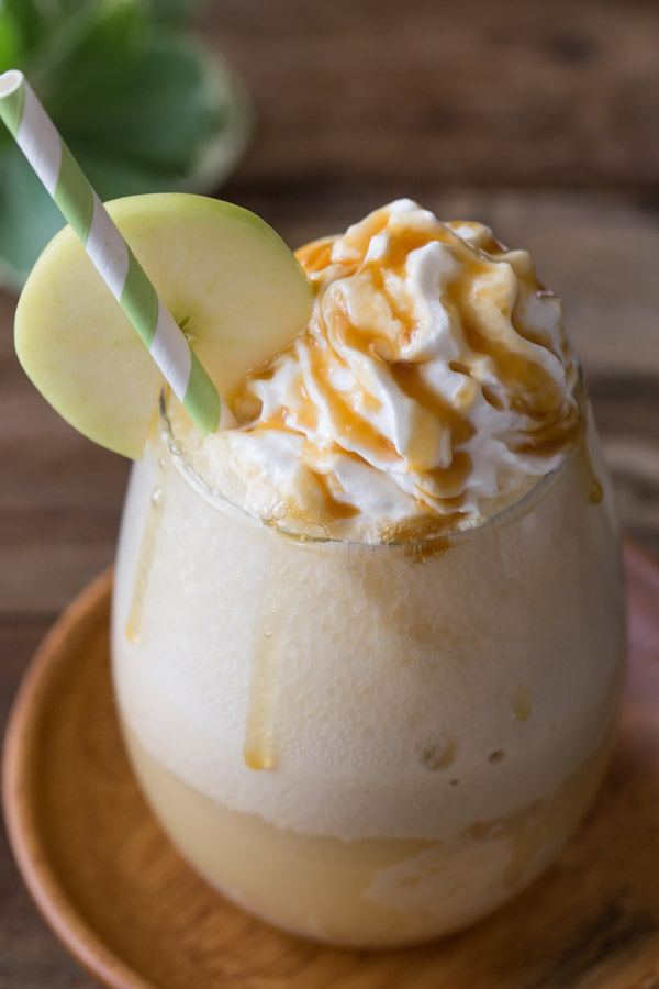 Caramel Apple Float topped with whipped cream and caramel, with a straw and an apple slice on the rim of the glass.