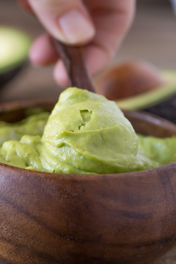 Whipped Avocado Cream in a small wood bowl, with a small wood spoon dipped into it.