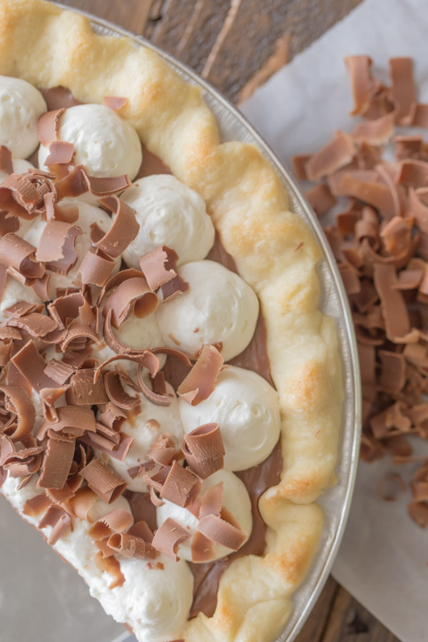 Homemade Chocolate Pudding Pie - Rich, creamy homemade chocolate pudding topped with whipped cream and piled with milk chocolate curls.