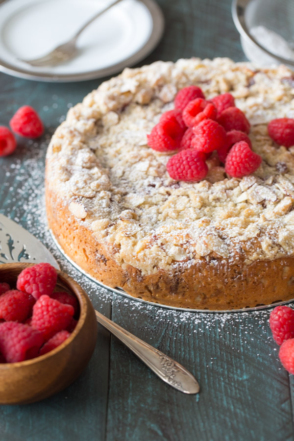 Raspberry Almond Coffee Cake garnished with powdered sugar and fresh raspberries.