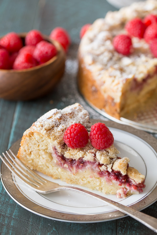 A slice of Raspberry Almond Coffee Cake garnished with powdered sugar and fresh raspberries on a plate with a fork, with the rest of the cake and a bowl of fresh raspberries in the background.