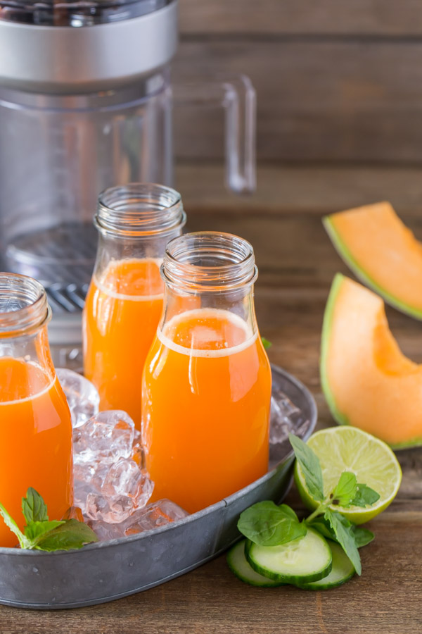 Cucumber Melon Refresher in three glass jars sitting in a tray with ice, with cucumber slices, a halved lime and cantaloupe slices next to the tray.
