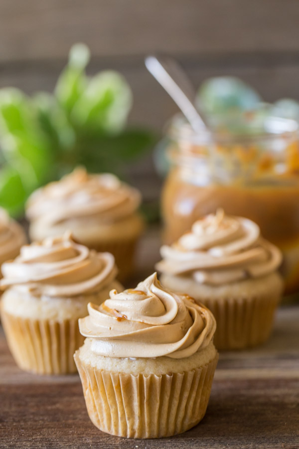 Apple Cupcake With Dulce De Leche Buttercream, with more cupcakes in the background along with a mason jar of dulce de leche.