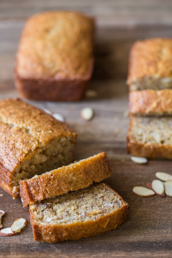 Healthier Banana Bread mini loaf that has been sliced, with a whole mini loaf and another sliced mini loaf in the background.