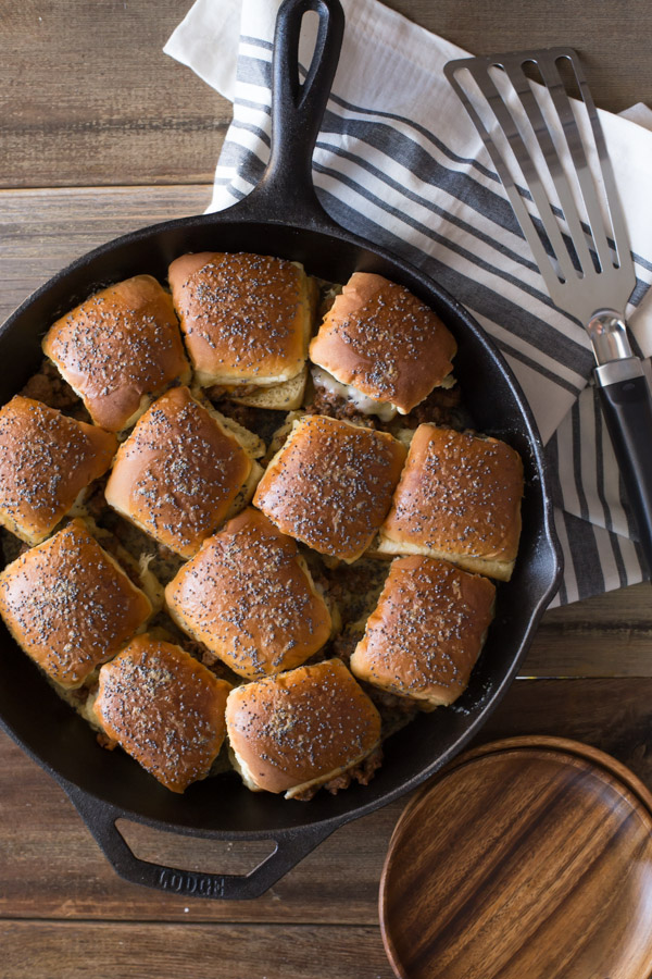 Party Bun Style Sloppy Joes in a cast iron skillet, with a serving spatula and some wood plates next to the skillet.