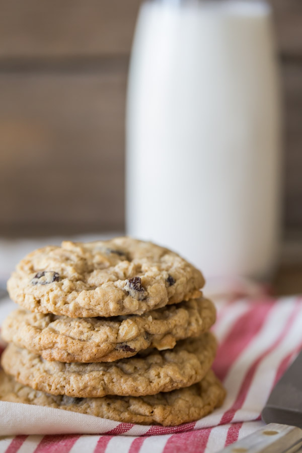Pumpkin Pie Spice Oatmeal Raisin Cookies stacked in a pile of four, with a glass of milk in the background.
