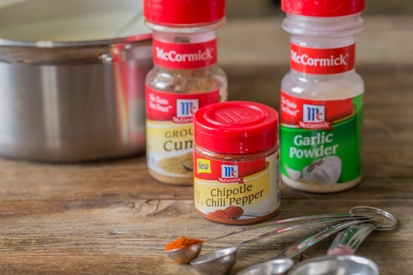 A container of McCormick Ground Cumin, a container of McCormick Chipotle Chili Pepper and a container of McCormick Garlic powder, with some measuring spoons and a sauce pan.