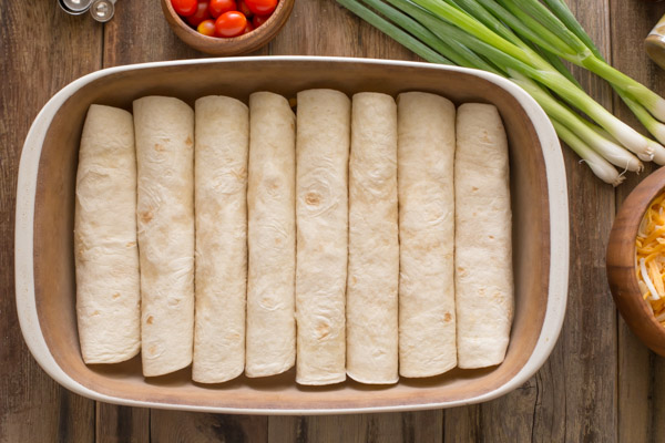 A baking dish with the stuffed, rolled tortillas in it, with other ingredients for the Breakfast Enchilada Bake next to the baking dish.