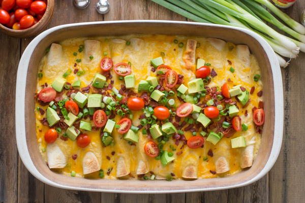 Breakfast Enchilada Bake with toppings in a baking dish, with grape tomatoes, measuring spoons, green onions, and a spice container next to the baking dish.