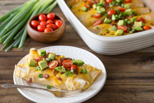 Breakfast Enchilada Bake on a plate with a fork, with the baking dish of the Breakfast Enchilada Bake in the background along with grape tomatoes and green onions.