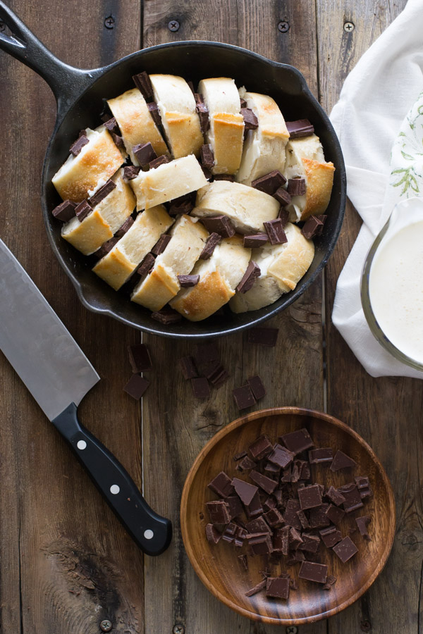 Bread and chocolate chucks arranged in a cast iron skillet, with a wood dish of chopped chocolate next to it, along with a knife and a glass cup of the cream mixture for the Chocolate Almond Bread Pudding.