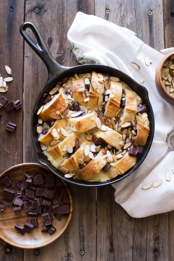 Chocolate Almond Bread Pudding in a cast iron skillet, with chopped chocolate and slivered almonds next to it.