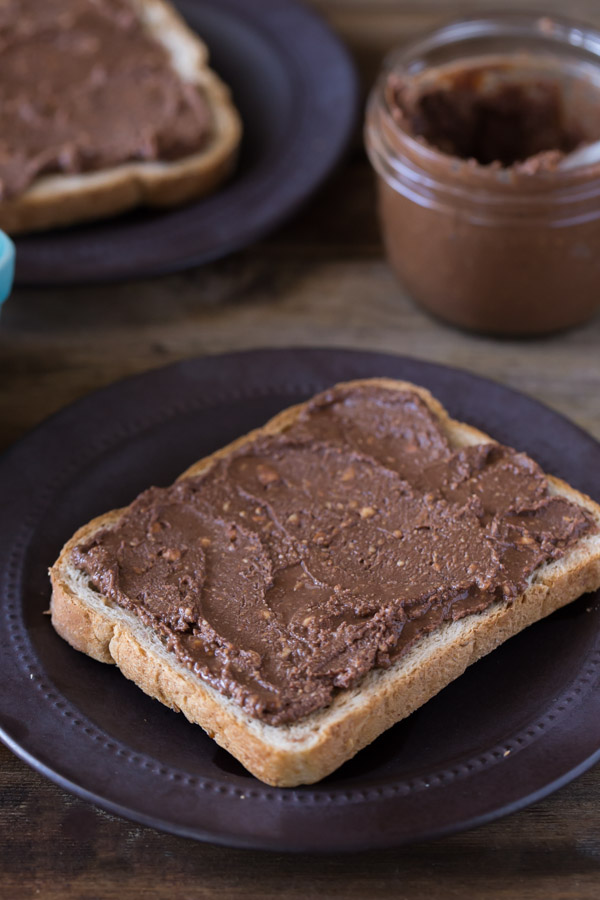 A piece of toast with Chocolate Hazelnut Butter spread on it, sitting on a plate, with a jar of Chocolate Hazelnut Butter in the background with another piece of toast with spread on it.