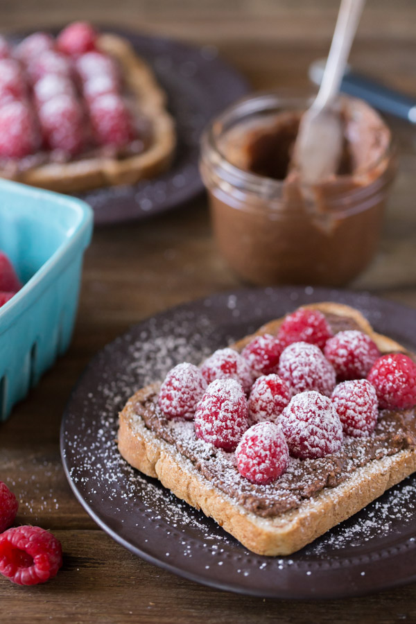 Chocolate Hazelnut Raspberry Toast sprinkled with powdered sugar on a plate, with a jar of Chocolate Hazelnut Butter in the background along with another plate of Chocolate Hazelnut Raspberry Toast sprinkled with powdered sugar.