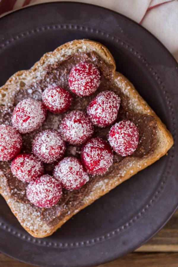 Chocolate Hazelnut Raspberry Toast sprinkled with powdered sugar on a plate.